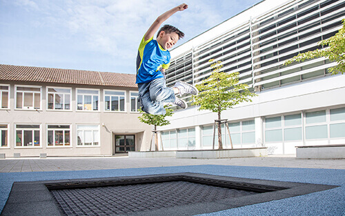 boy jumping on playground trampoline