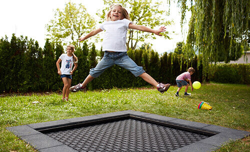 girl jumping on playground trampoline